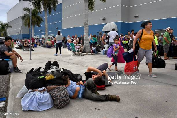 Tired families wait in the outer area of the Germain Arena for a shelter spot The Germain Arena in Estero Florida became a shelter for storm refugees...