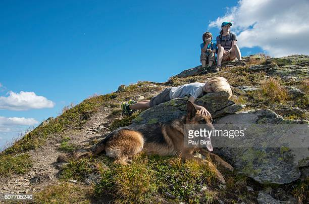 Tired family, together with a dog (german shepherd), sitting on the rock,  to exhausted to continue.