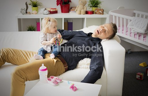 Tired father sleeping with baby on his lap. : Stock Photo