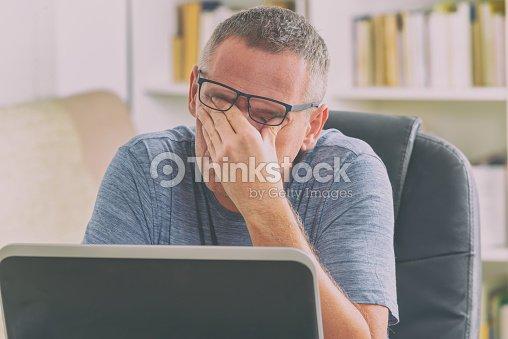 Tired freelancer man rubbing his eyes : Stock Photo