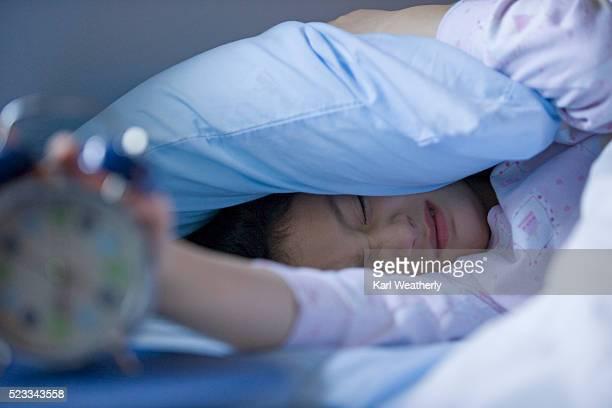Tired Girl Turning Off Alarm