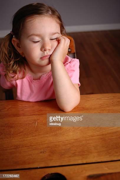 Tired Little Girl Falling Asleep in a School Desk