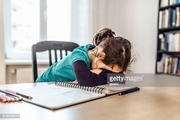 Stanco bambina sul tavolo con schizzi e matite di colore