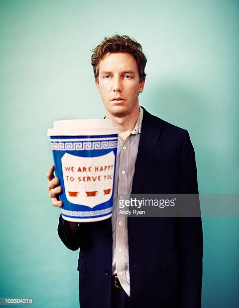 Tired man holding giant cup of coffee
