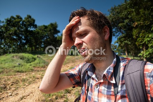 Tired Man in forest unfder strong sun with backpack. Travel in Asia alone. Suffer form sunstroke : Stock Photo