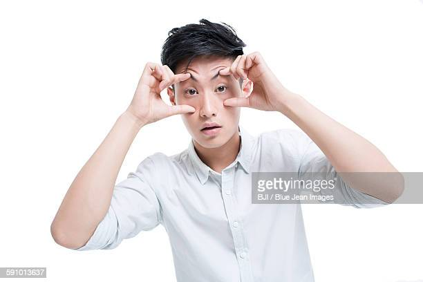 Tired man propping his eyes with hands
