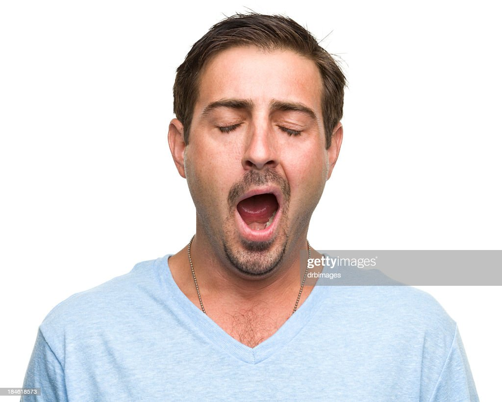 A tired man wearing a blue top is yawning