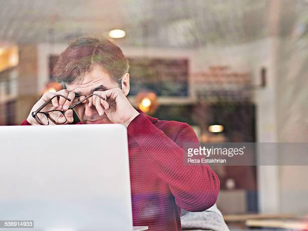 Tired man working on laptop