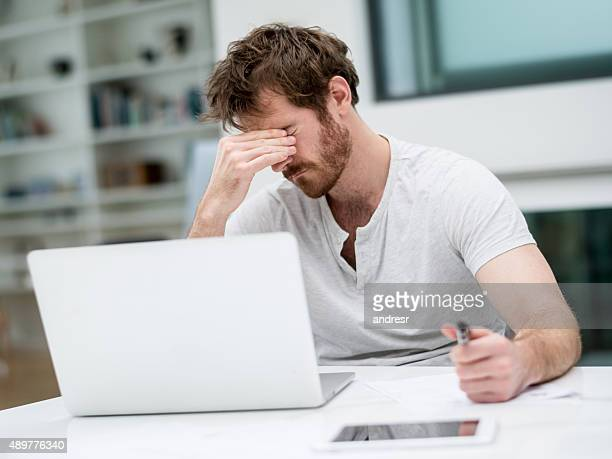 Tired man working online at home