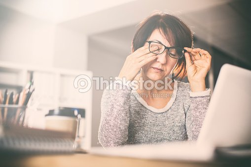 Tired middle age woman rubbing eyes : Stock Photo