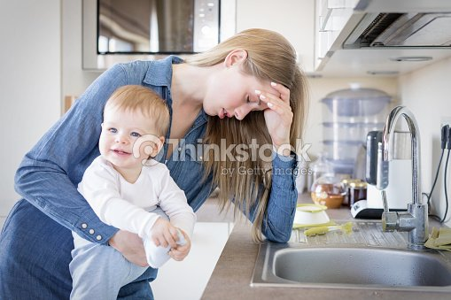 Tired mom with baby in her arms standing by the sink : Stock Photo