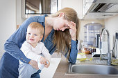 Tired mom with baby in her arms standing by the sink