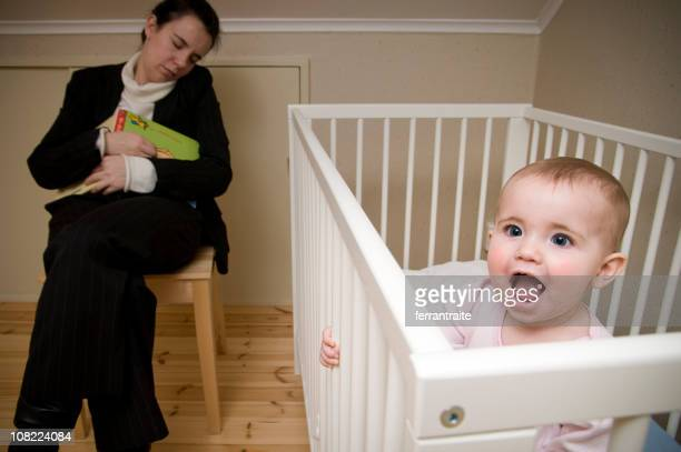 Tired Mother Asleep While Baby is Awake in Crib
