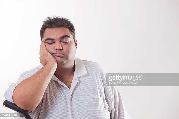Tired obese man with hand on chin over white background