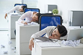 Asian business people sleeping at their workplaces