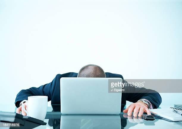 Tired or broken down businessman behind laptop