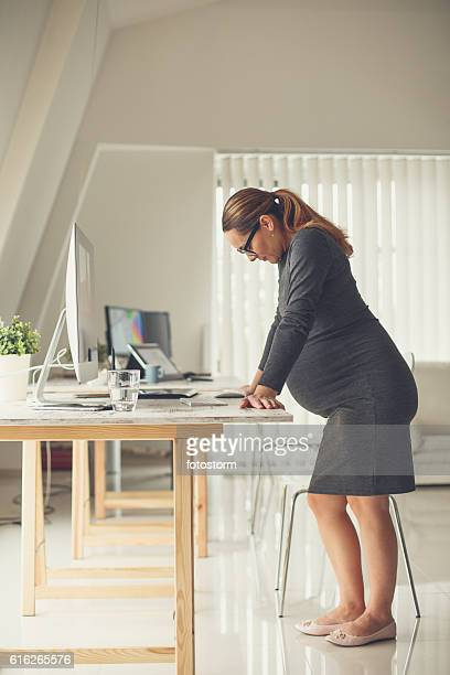 Tired pregnant business woman in the office