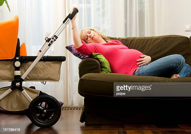tired pregnant mammy rocking the stroller
