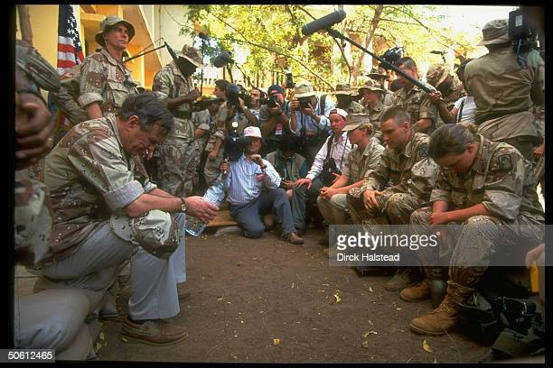 Tired Pres Bush hunching over w water bottle camouflagic jacket blending in w uniforms of US OP Restore Hope soldiers mtg w him amid press circle