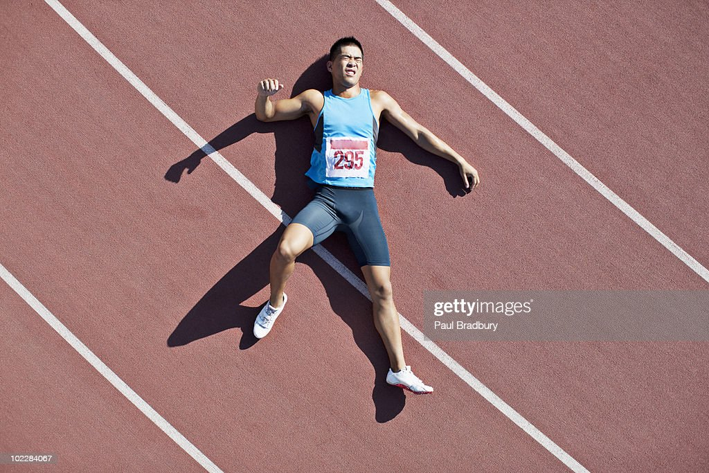 Tired runner laying on track : Stock Photo