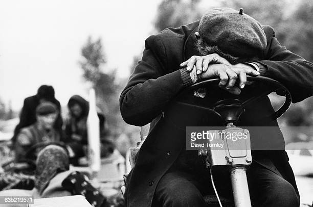 A tired Serb refugee rests his head on the steering wheel of his family's tractor while on the road He and his family loaded as much as they could on...
