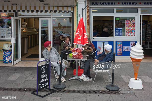 Tired sikh gentlemen rest outside an ice cream parlour on 17th September 2016 on the Eastern Esplanade at Southend Essex England One sleeps and the...