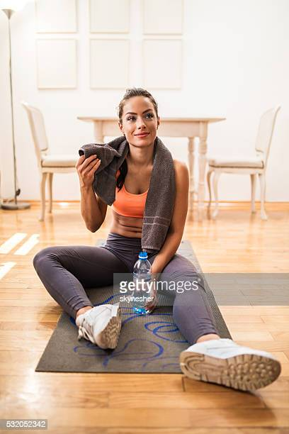Tired smiling woman relaxing on the floor after sports training.