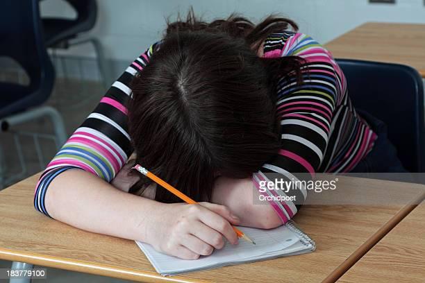 Fatigué d'étudiant pose sa tête dans une salle de classe