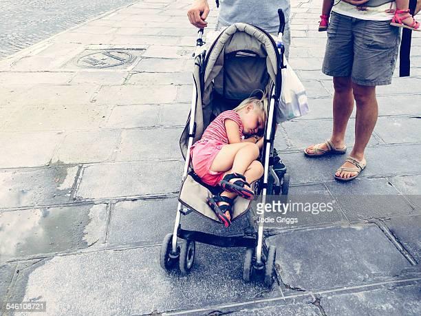 Tired toddler sleeping in stroller outside