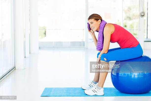 Tired Woman Cleaning Face While Sitting On Pilates In Gym