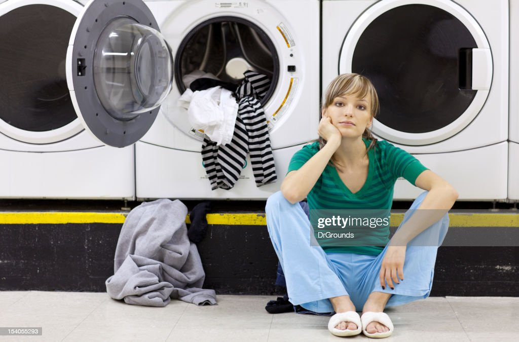 Tired woman doing laundry in laundromat : Stock Photo
