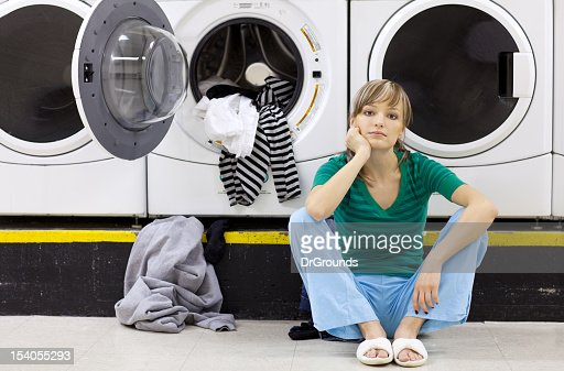 Tired woman doing laundry in laundromat : ストックフォト