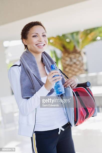 Tired woman drinking water after playing tennis