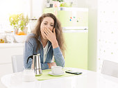 Tired lazy woman having breakfast at home in the kitchen, she is yawning and having a coffee