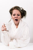 tired woman holding coffee cup in her hand and wearing a white robe wearing