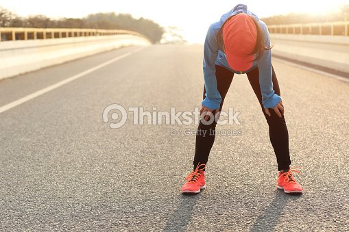 tired woman runner taking a rest after running hard : Stock Photo