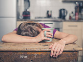 A tired young woman is having a cup of tea and is resting her head on a table