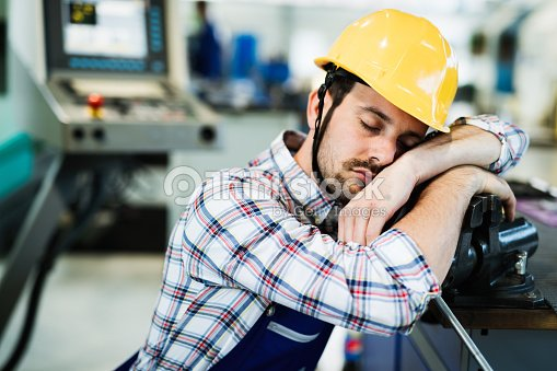Tired worker fall asleep during working hours in factory : Stock Photo