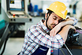 Tired overworked worker falls asleep during working hours in factory