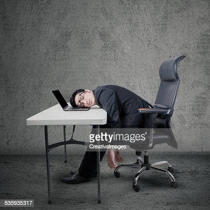 Tired worker sleeping on laptop at desk : Stock Photo