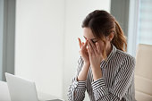 Tired young woman massaging nose bridge at workplace. Businesswoman experiences discomfort from long work at computer. Bad eye vision concept