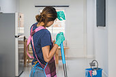 Tired young woman standing at living room with cleaning products and equipment, Housework concept