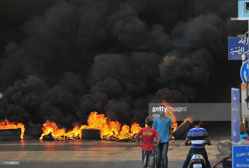 Tires burn across a street in the northern city of Tripoli, on June 23, 2013, during protests in support of Sunni Muslim Sheikh Ahmad al-Assir whose supporters have clashed with the Lebanese army in the southern Lebanese city of Sidon. Two Lebanese army officers and a soldier were killed in the clash with supporters of the radical Sunni Muslim Sheikh opposed to the powerful Shiite movement Hezbollah, an army statement said. AFP PHOTO / IBRAHIM CHALHOUB