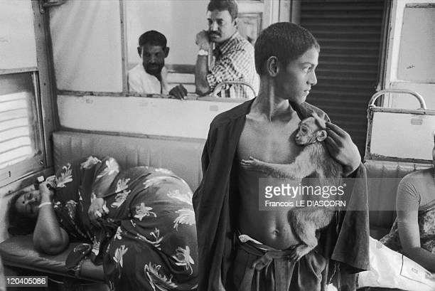 Tirupati India A child with a monkey in a train near Tirputati Andhra Pradesh