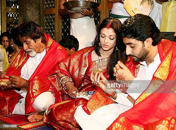 Indian actors Abhishek Bachchan and Aishwarya Rai are accompanied by Amitabh Bachchan as they take prasad during a visit to The Lord Venkatesh Wara...