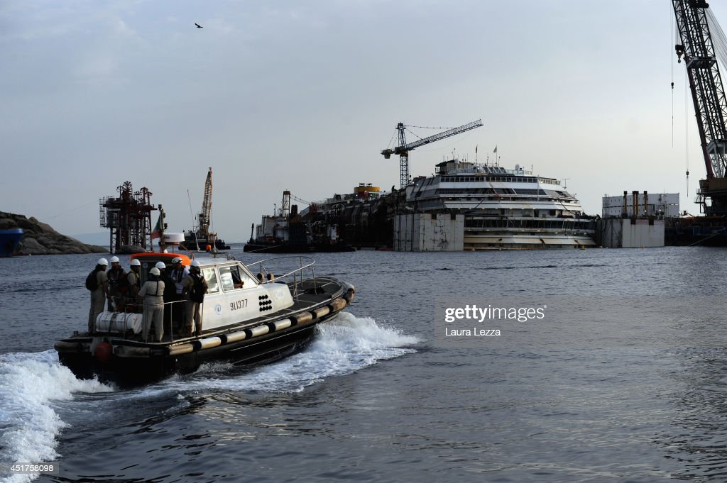 Titan- Micoperi workers are seen with the sunken ship Costa Concordia the day after the last sponson is installed on the port side of the wrecked ship Costa Concordia on July 4, 2014 in Isola del Giglio, Italy. A total of 30 sponsons have been attached to the Costa Concordia to re-floate the ship wreck around July 10th. The wreckage will be removed by the end of July 2014 and will be toed to the port of Genoa for dismantling.