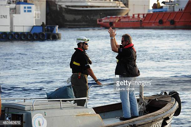 Titan Senior Salvage Master Nick Sloane greets workers before the departure of the wrecked cruise ship Costa Concordia on July 23 2014 in Isola del...