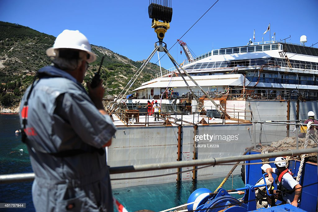 Titan workers are seen while the last sponson is installed on the port side of the wrecked ship Costa Concordia on July 3, 2014 in Isola del Giglio, Italy. A total of 30 sponsons have been attached to the Costa Concordia to re-floate the ship wreck around July 10th. The wreckage will be removed by the end of July 2014 and will be toed to the port of Genoa for dismantling.