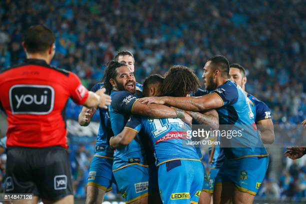 Titans players celebrate a try by Pat Politoni during the round 19 NRL match between the Gold Coast Titans and the Cronulla Sharks at Cbus Super...