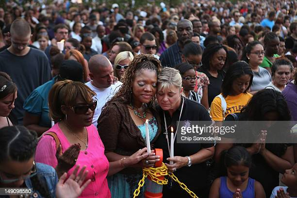 Titia Stillwell and Lori Meade embrace and pray with thousands of others during a prayer vigil for the victims of Friday's movie theater mass...